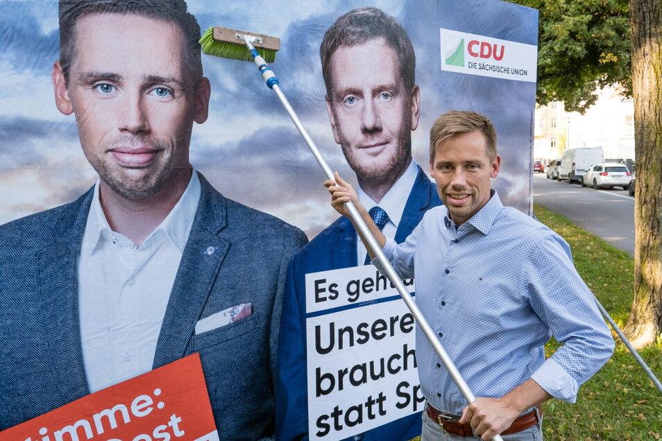 CDU-Kandidat Florian Oest klebt ein neues Wahlwerbeplakat auf der Goethestraße in Görlitz.