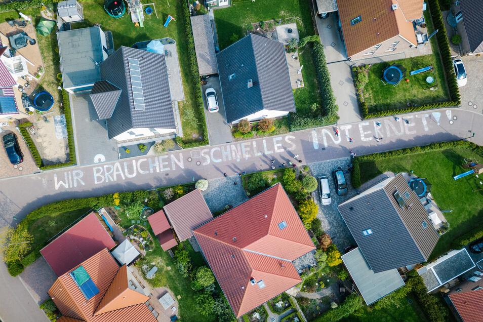 """""""Wir brauchen schnelles Internet!!"""" steht in großen Buchstaben aus Kreide in einem Wohngebiet in Niedersachsen."""