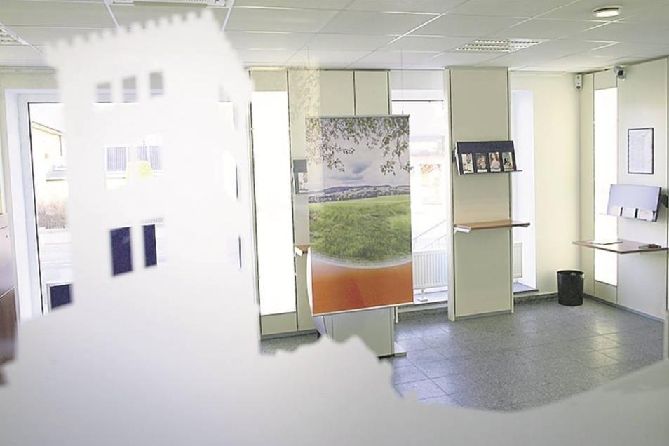 Der Serviceraum mit dem Schalter und der Selbstbedienungstechnik – fotografiert durch eine der Glastüren mit dem Bild des Valtenbergturmes.
