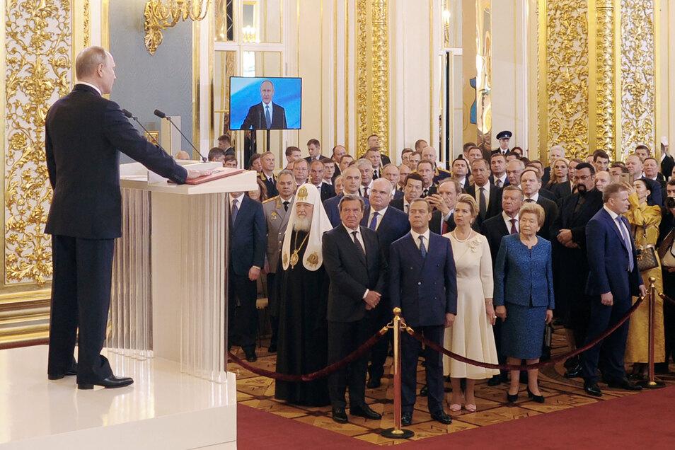 Wladimir Putin (l), Präsident von Russland, spricht bei seiner Amtseinführung als neuer Präsident iim Mai im Kreml, während er seine Hand auf die Verfassung legt.