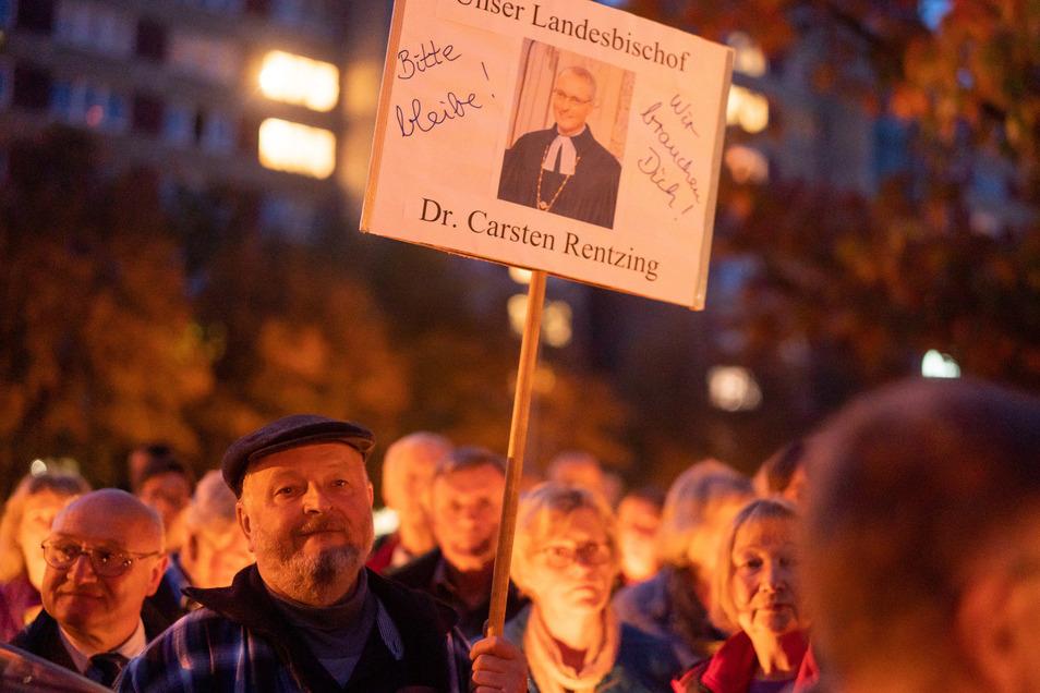 Zahlreiche Menschen stehen vor dem Landeskirchenamt in Dresden bei einer Mahnwache zusammen.