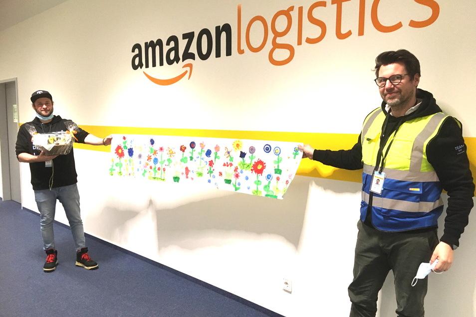 Der alte und der neue Standortleiter von Amazon Lampertswalde: Tim Stapf (l.) geht, Henry Börnicke ist gekommen. Beide zeigen die Geschenke der Kita.