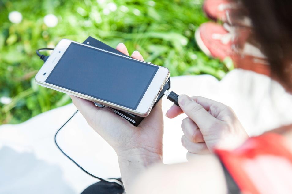 Frische Luft und warmer Sonnenschein: Während vielleicht ein Eis die Besitzerin erfrischen könnte, freut sich das leere Handy über Energie aus der Powerbank - doch zu heiß sollte es nicht werden.