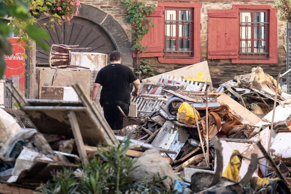 Anwohner laufen in der Innenstadt von Ahrweiler durch Unrat und aufgetürmte Einrichtungsgegenstände aus den zerstörten Häusern und Wohnungen. Dort helfen jetzt die Sachsen.