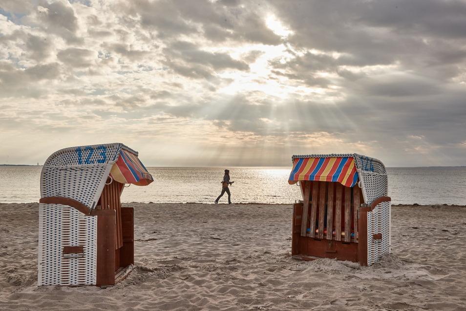 Schleswig-Holstein, Scharbeutz: Eine Frau joggt am Strand entlang. Schleswig-Holstein öffnet heute unter Auflagen für Touristen.