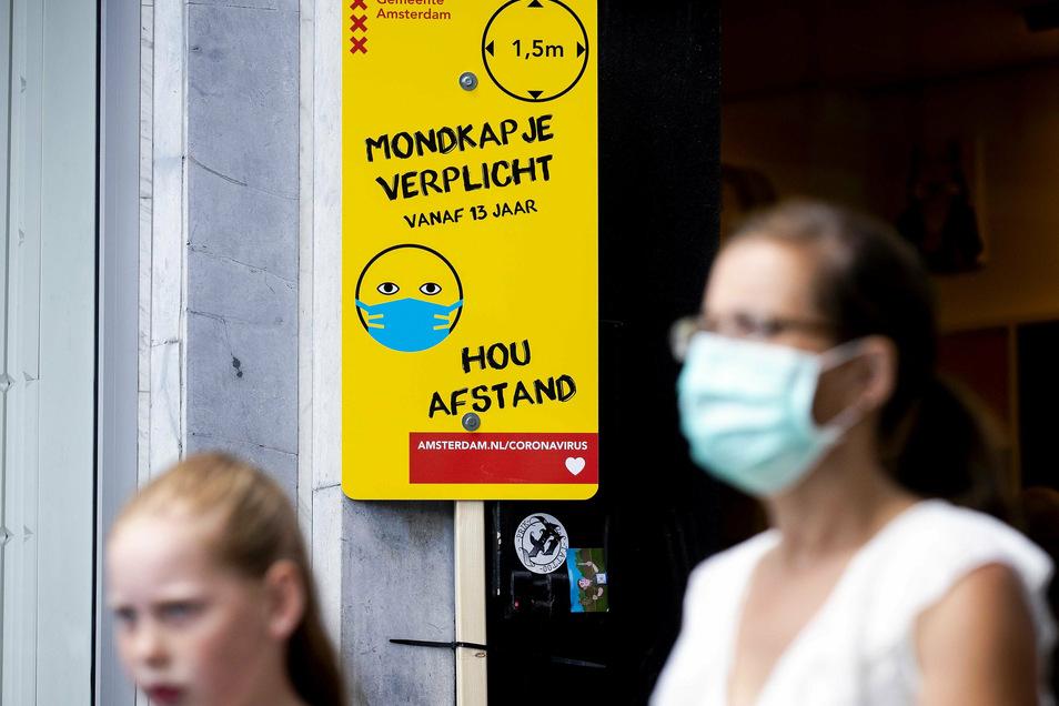 Eine Frau mit Mundschutz geht in Amsterdam an einem Schild mit Informationen über die Maskenpflicht vorbei.