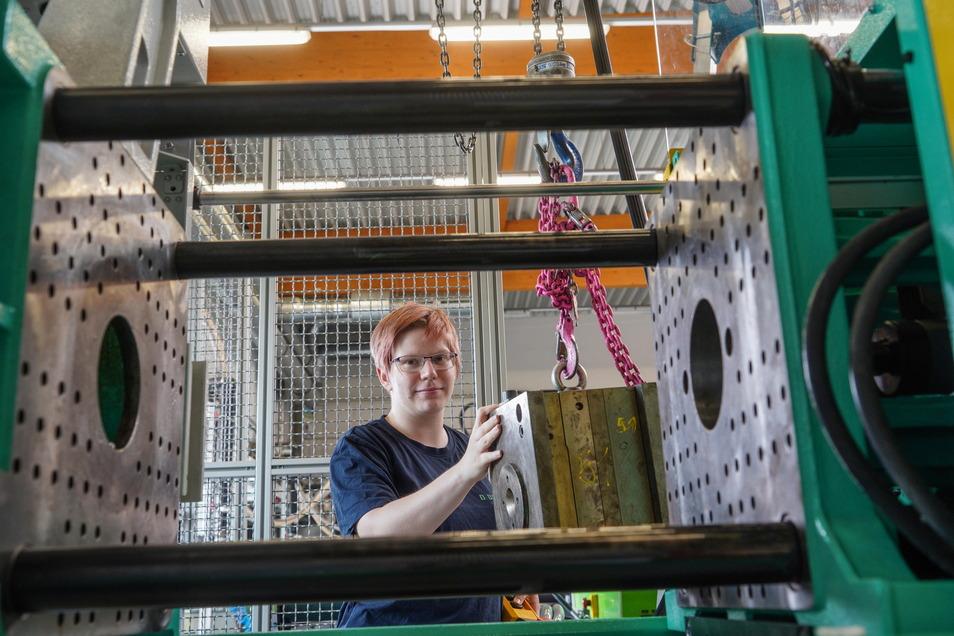Im Bautzener Polysax-Ausbildungszentrum setzt Emily Hoffmann ein Werkzeug in eine Spritzgussmaschine ein. Sie absolviert eine Ausbildung zur Verfahrensmechanikerin und befindet sich im zweiten Lehrjahr.