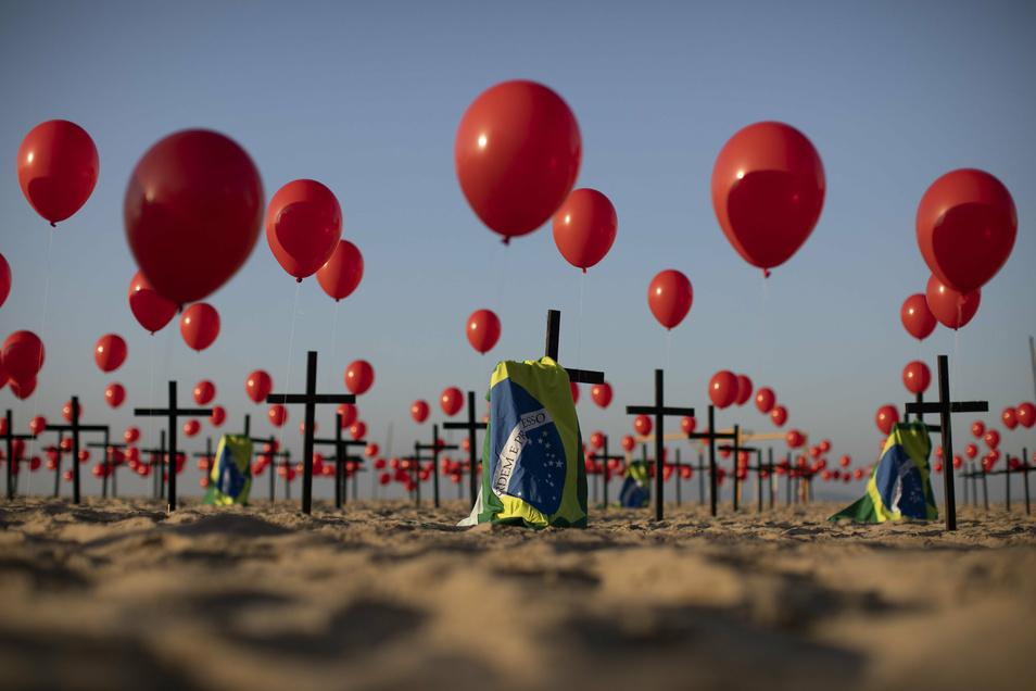 """Die Nichtregierungsorganisation """"Rio de Paz"""" platzierte zum Gedenken der Opfer der Covid-19-Pandemie 1.000 rote Luftballons und 100 Kreuze am Strand der Copacabana."""