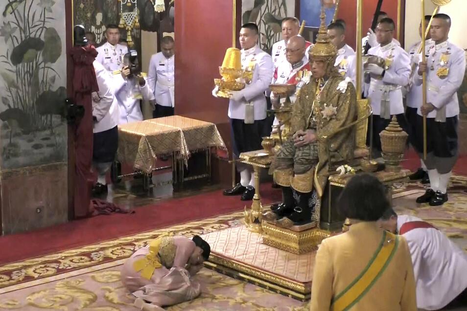 Königin Suthida kniet ehrerbietig vor dem neuen König.