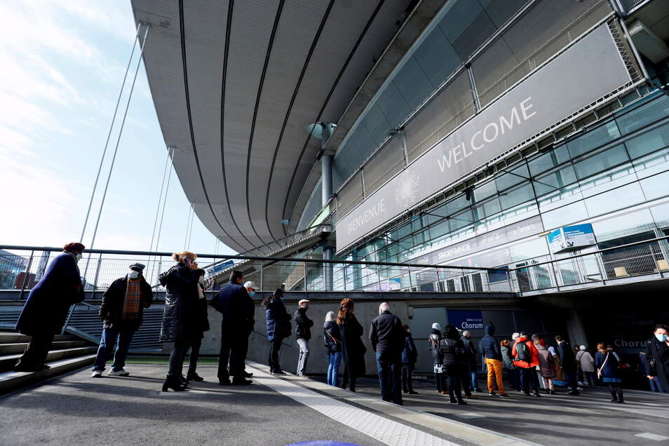 Menschen stehen in einer Schlange vor dem Stade de France, um sich gegen das Coronavirus impfen zu lassen.