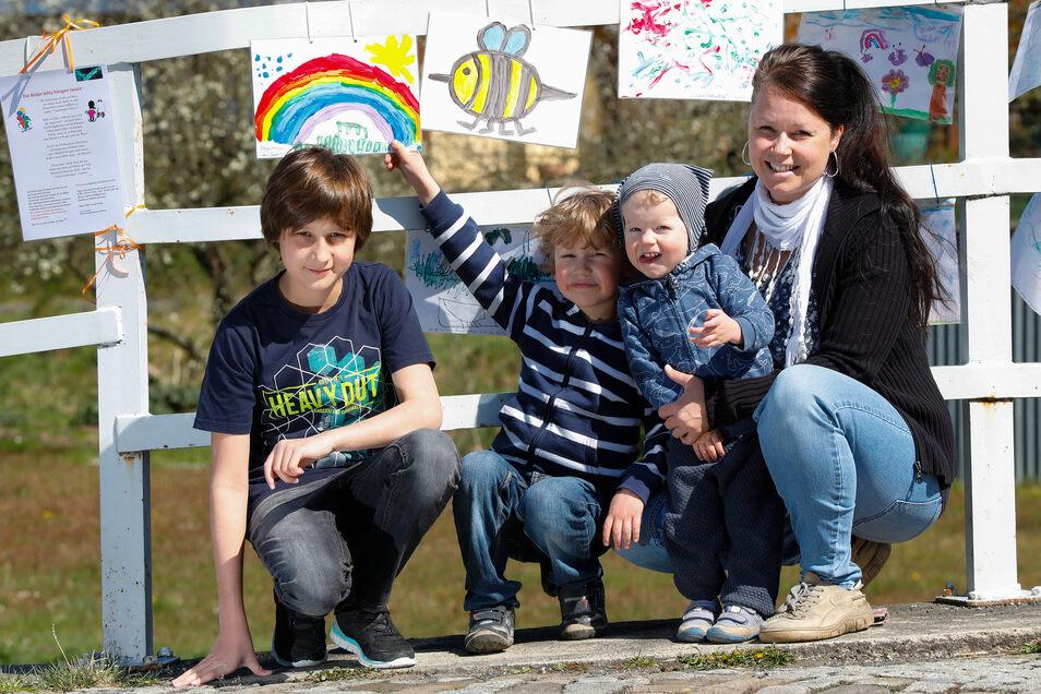 """Sabine Engel hat mit ihren drei Kindern Ruben, Carl und Leonas (von rechts) neue Bilder an die """"Landwasser-Galerie"""" angebracht. Der eineinhalbjährige Leonas und der fünfjährige Carl sind stolz auf ihre Bilder."""