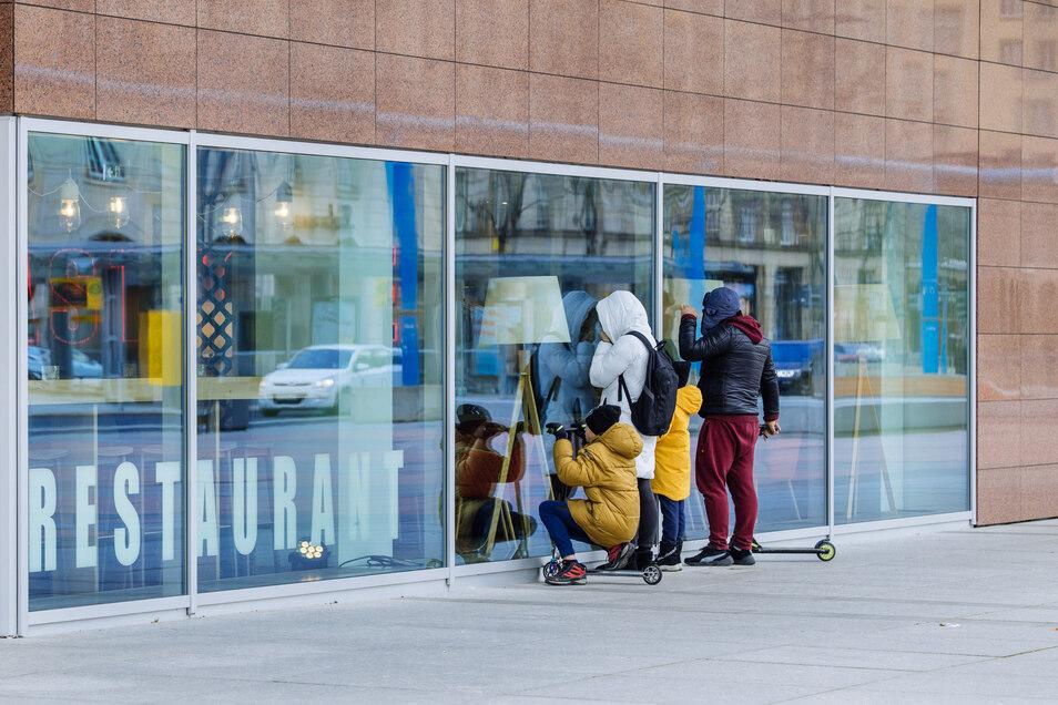 Eine Familie in Dresden schaut durch eine Glasfront in ein geschlossenes Restaurant. Im Kampf gegen die Ausbreitung des neuartigen Coronavirus gelten in Dresden jetzt auch verschärfte Regeln für das Verlassen der Wohnung.