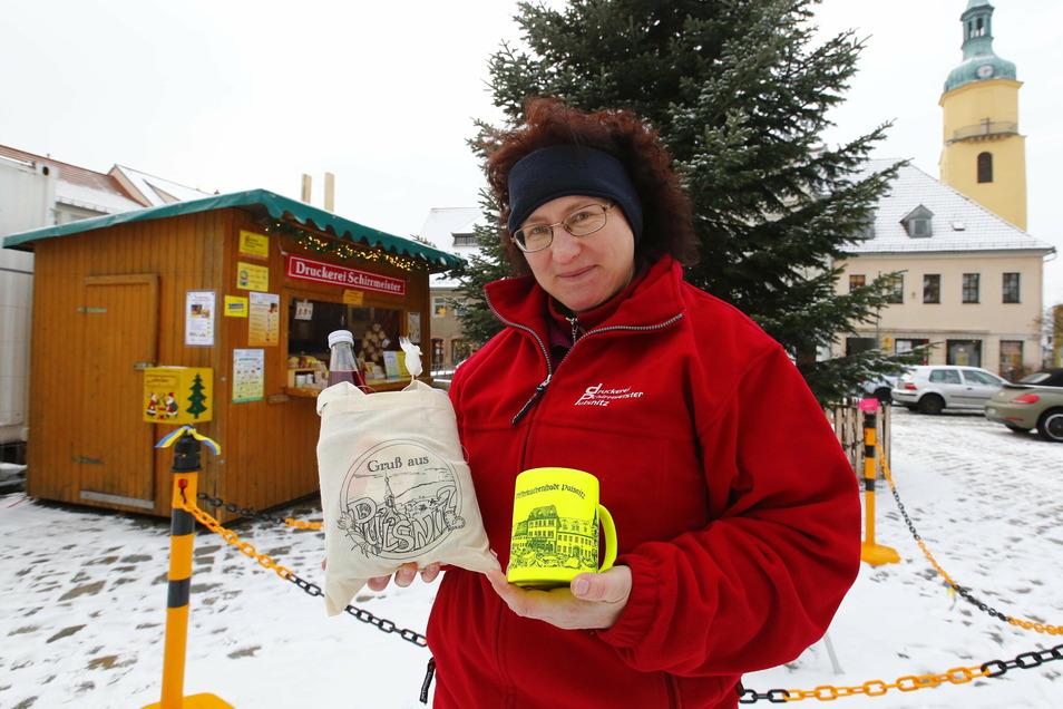 Die Glühweinbude auf dem Markt in Pulsnitz ist geöffnet. Ria Schirrmeister zeigt, was es unter anderem zu kaufen gibt.
