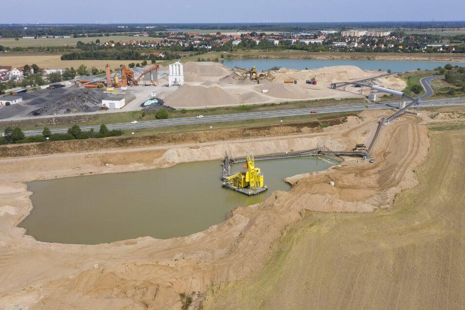 Eine Ansicht vom vergangenen August. Mittlerweile ist der Kiessee südlich der B 169 schon deutlich größer. Hinter dem blauen See liegt die Bahnstrecke Dresden-Leipzig, dahinter Zeithain.