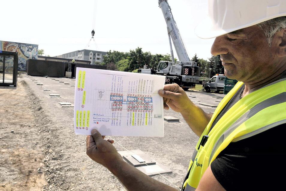 Bauleiter Yeni Ali zeigt den Plan mit den 36 Containerstellplätzen für das Interimsquartier der Kita Ulja. Die Adapteo GmbH aus Frankfurt am Main hatte in der europaweiten Ausschreibung das günstigste Angebot vorgelegt und war deutlich unter der Kosten