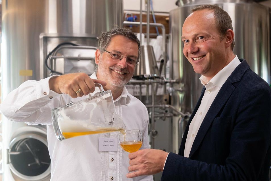 Stefan Oettel (links) braut Bier in Lohmen. Sachsens Landwirtschaftsminister Wolfram Günther erfuhr dort von Lebensmittelherstellern, welche Wünsche sie an Händler und Kunden haben.