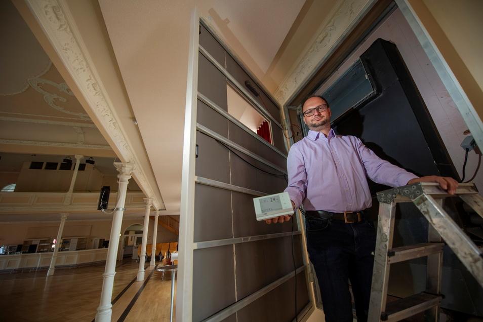 Der Chef der Coswiger Börse, Thomas Kretschmer, steht an einem Klimaumluftgerät im großen Saal des Veranstaltungshauses auf der Leiter, welches mit einem UV-Filter zur Virenabtötung ausgerüstet werden soll. Auch soll im Saal mittels moderner Technik