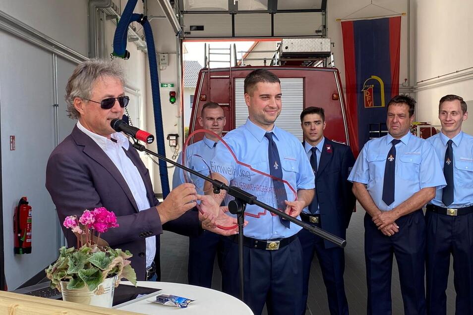 Bürgermeister Jochen Reinicke übergibt einen symbolischen Glasschlüssel für das neue Gerätehaus an Ortswehrleiter Philip Wendt.