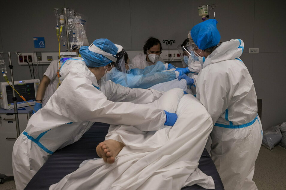 """Ein medizinisches Team des neuen """"Krankenhauses für Pandemien"""" in Madrid dreht auf der Corona-Intensivstation einen Patienten in seinem Bett auf die andere Seite."""