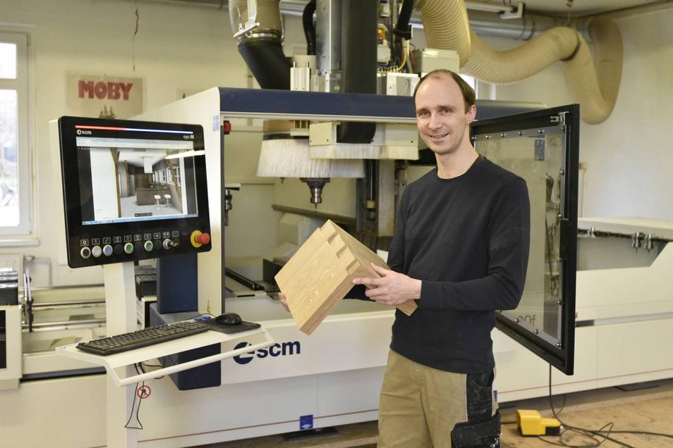 Tischlermeister Peter Stenzel aus Hartmannsdorf, zeigt an seinem neuen CNC-Bearbeitungszentrum eine sogenannte Zinkung aus Eiche.