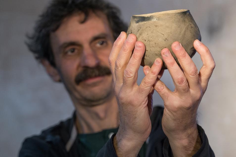 Chefarchäologe an einer spektakulären Ausgrabung:  Harald Stäuble präsentiert eine mehr als 7.000 Jahre alte Schale, gefüllt mit Nahrung. Und diese wurde geopfert.