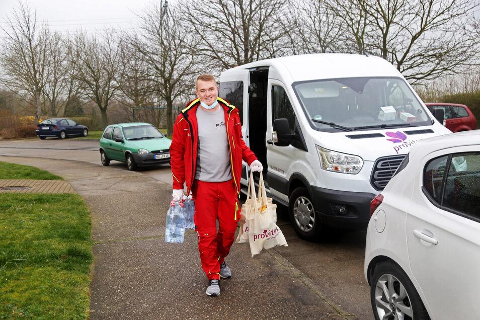 Nico Michael an der Potsdamer Straße in Riesa. Der Mitarbeiter des Fahrdienstes Provitus hat zwei Beutel voll Lebensmittel und einige Flaschen Wasser für eine Riesaerin eingekauft, die krebskrank ist und deshalb nicht vor die Tür soll.