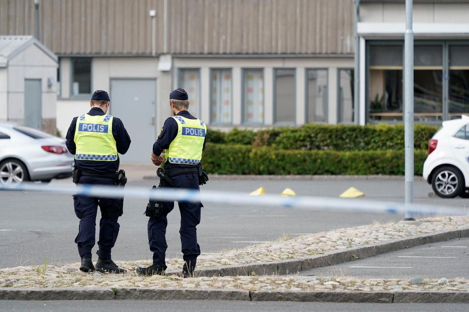 Zwei Polizisten stehen am Tatort nach mutmaßlichen Schüssen in Kristianstad auf einem Parkplatz.