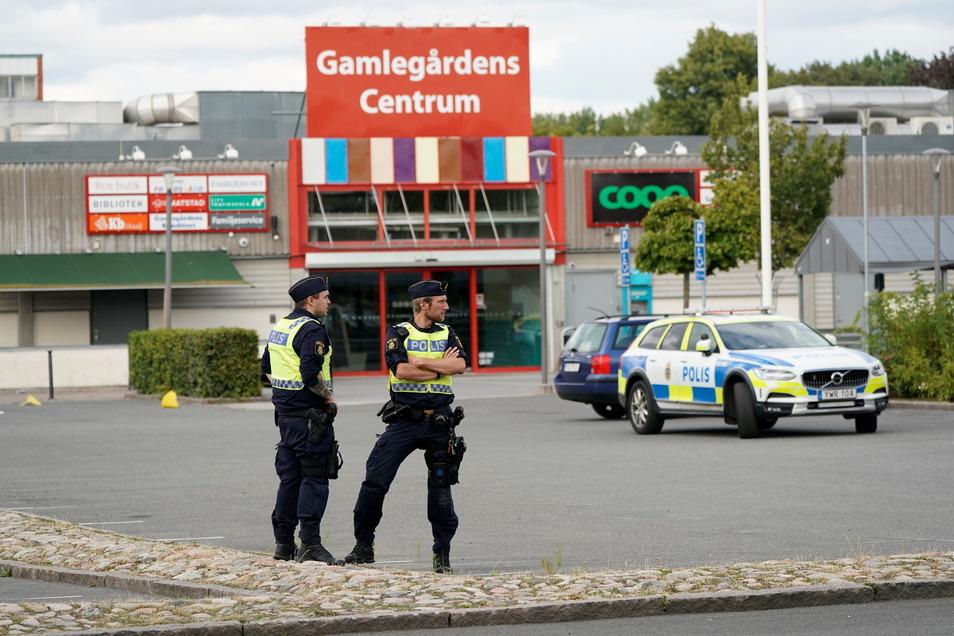 Zwei Polizisten stehen nach Schüssen in Kristianstad an einem Tatort.