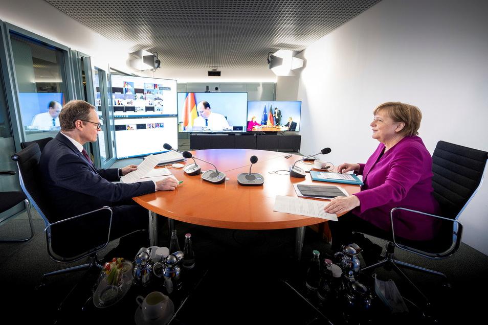 Bundeskanzlerin Angela Merkel (CDU) und der Regierende Bürgermeister von Berlin, Michael Müller (SPD), sitzen zu Beginn der Videokonferenz mit den Ministerpräsidentinnen und Ministerpräsidenten der Länder zusammen.