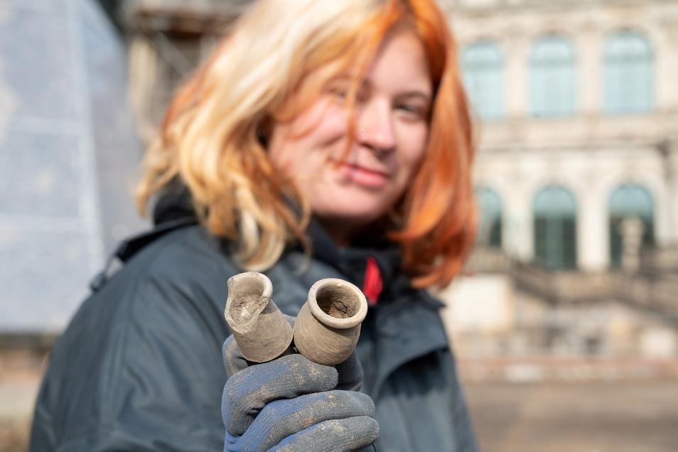 Grabungsarbeiterin Fara Freitag zeigt aus dem Untergrund geborgene Keramikgefäße, in denen früher Salben aufbewahrt wurden.