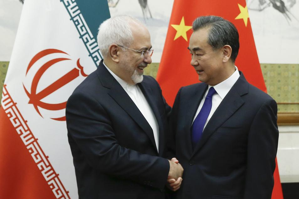 Der chinesische Außenminister Wang Yi (l.)) bei einem Treffen mit dem iranischen Außenminister Sarif in Peking. Auch um eine enge Kooperation der beiden Länder anzubahnen.