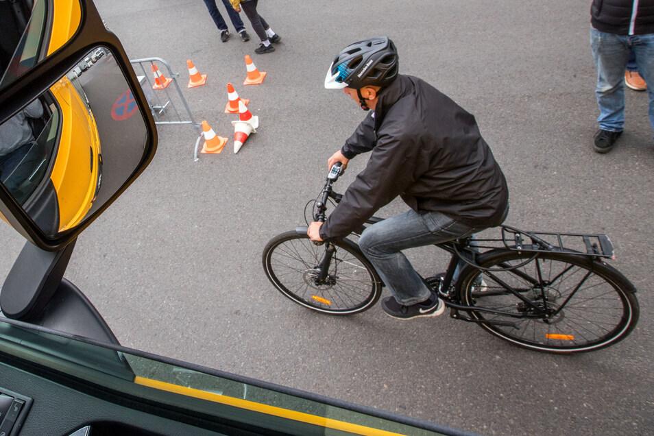 Ein Fahrradfahrer fährt während einer Demonstration des neuen Abbiegeassistenten neben einem Lastwagen.