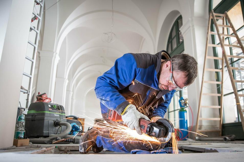 Im Eingangsbereich im Französischen Pavillon werden derzeit die letzten Bauarbeiten ausgeführt. Bauschlosser David Träber bearbeitet hier einen Metallrahmen über einem Verteiler der Fußbodenheizung.