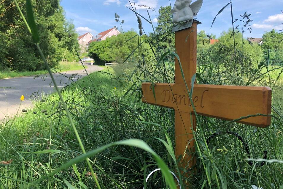 """""""Daniel"""" steht auf einem Holzkreuz und erinnert an den 24-Jährigen, der im Sommer 2020 nachts auf seinem Rad auf einem unbeleuchteten Weg nach Hause fuhr, als er im Dunkeln angegriffen und mit einem Messer getötet wurde."""