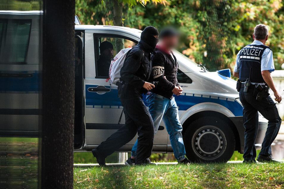 Mutmaßliche Rechtsterroristen, die am 1.10.2018 in  Sachsen festgenommen wurden, erreichen den Bundesgerichtshof und werden von Polizisten abgeführt.
