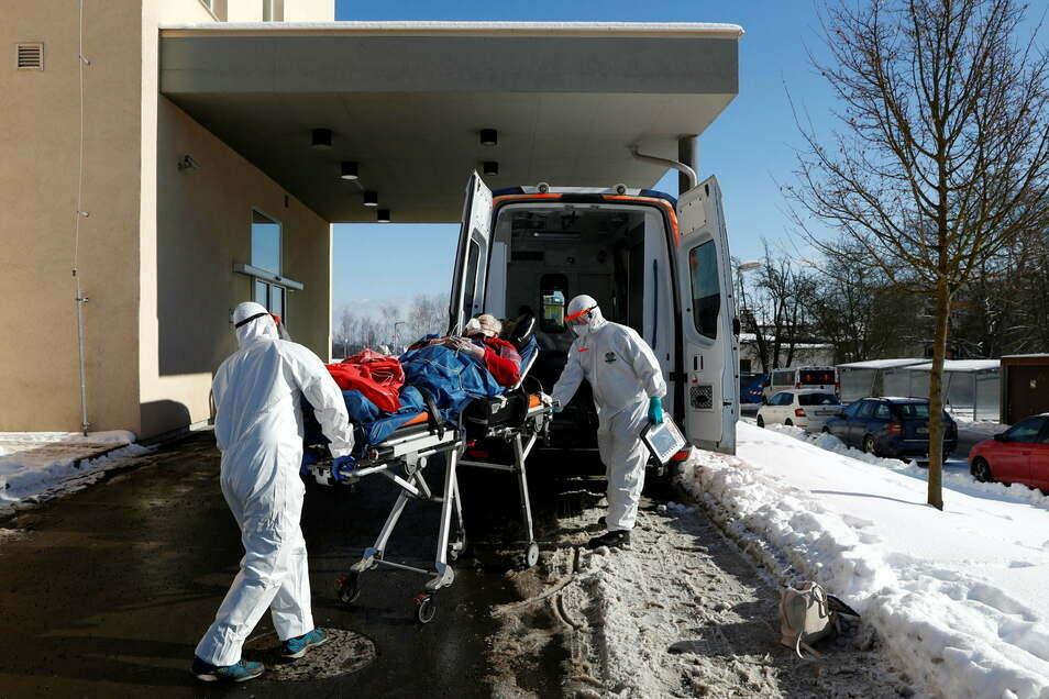 Medizinische Mitarbeiter in Schutzausrüstung transportieren eine Patientin auf einer Trage zu einem Krankenwagen vor einem Krankenhaus, das aufgrund einer hohen Anzahl an Coronapatienten überlastet ist.