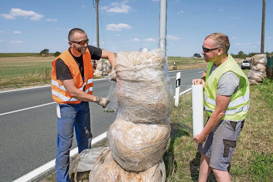 Alles muss verpackt sein: Zum Schutz der Motorradrennfahrer werden die Straßenränder zwischen Mautitz, Groptitz und Heideberg mit in Plastik verpackten Strohballen gesichert. Thomas Macioschek (l) und Lars Zieger gehören zu den Helfern.