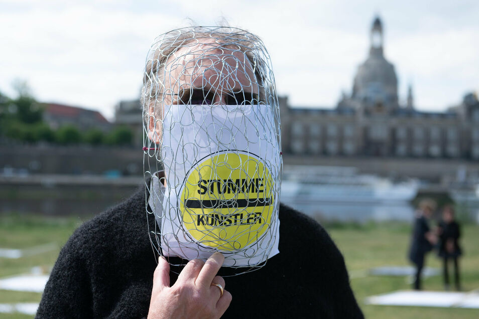 """Matthias Eckardt, Mitglied Freundeskreis Jazztage Dresden e.V., trägt während einer ersten Demonstration am 13. Mai mit dem Titel """"Stumme Künstler"""" am Elbufer eine Gittermaske."""