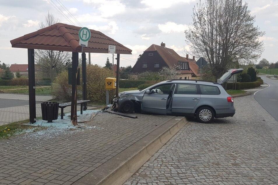 Ein Bild von der Unfallstelle: Die Front des VW ist komplett hinüber. Im Buswartehäuschen sind die Scheiben zertrümmert.