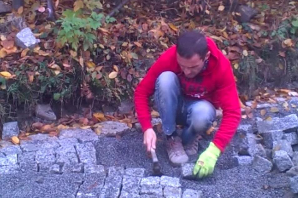 Obwohl Luis Mende seit 20 Jahren Steine verlegt, hat er keine Knieprobleme. Er arbeitet in der Hocke.