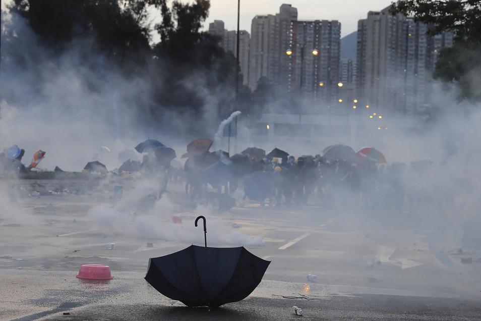 Ein Regenschirm liegt am 5. August 2019 auf einer Straße in Hongkong, während Demonstranten vor Tränengas in Deckung gehen.
