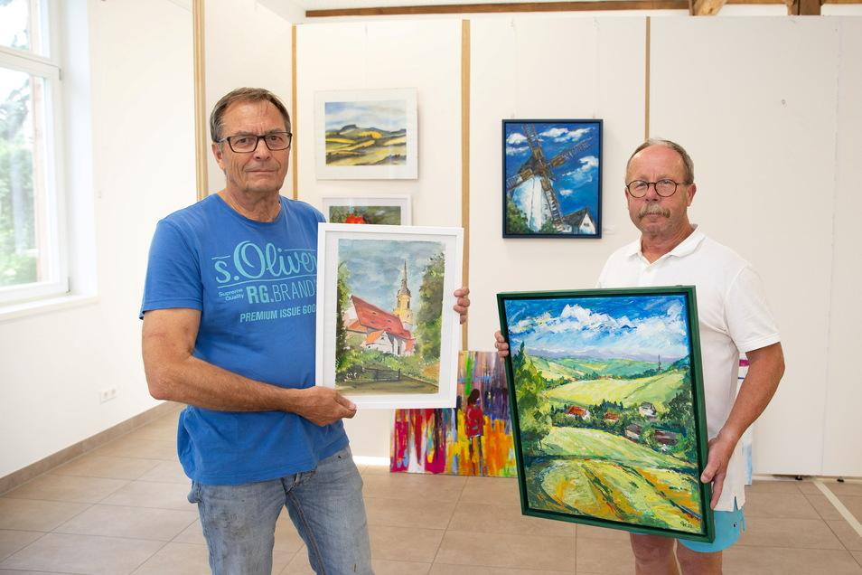 Jörg Arnhold (links) und Gunter Hauswald, hier mit Ansichten von Possendorf, bereiten eine Ausstellung von Hobbykünstlern in der Pfarrscheune des Bannewitzer Ortsteiles vor. Im Hintergrund ist eine der Galeriewände für die über 100 Arbeiten zu sehen.