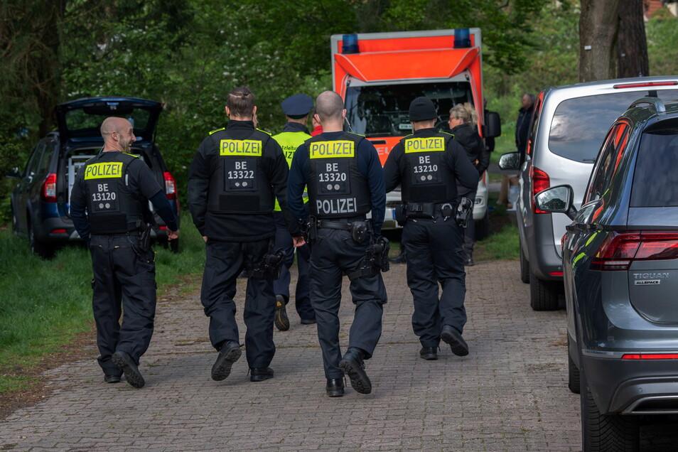 Polizeibeamte gehen auf einem Weg zu einer Parkanlage in Berlin-Zehlendorf. Dort wurde am frühen Morgen des Sonnabends ein schwer verletzter Mann gefunden.