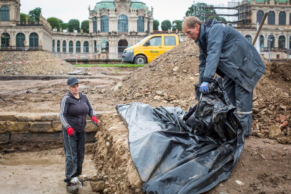 Katrin Ruffani und Fred Seidel beseitigen die Plane, die die freigelegten Grundmauern schützt. Hier wurden bei den Grabungen Fundamente des alten Reithauses und der alten Zwingergrotte entdeckt.