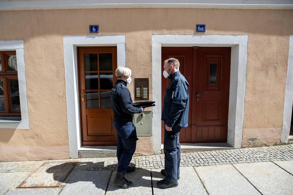 Wenn das Ordnungsamt klingelt: Hier checken die Bediensteten Hantsche (l.) und Härtel, ob der Bewohner wirklich in Quarantäne ist.