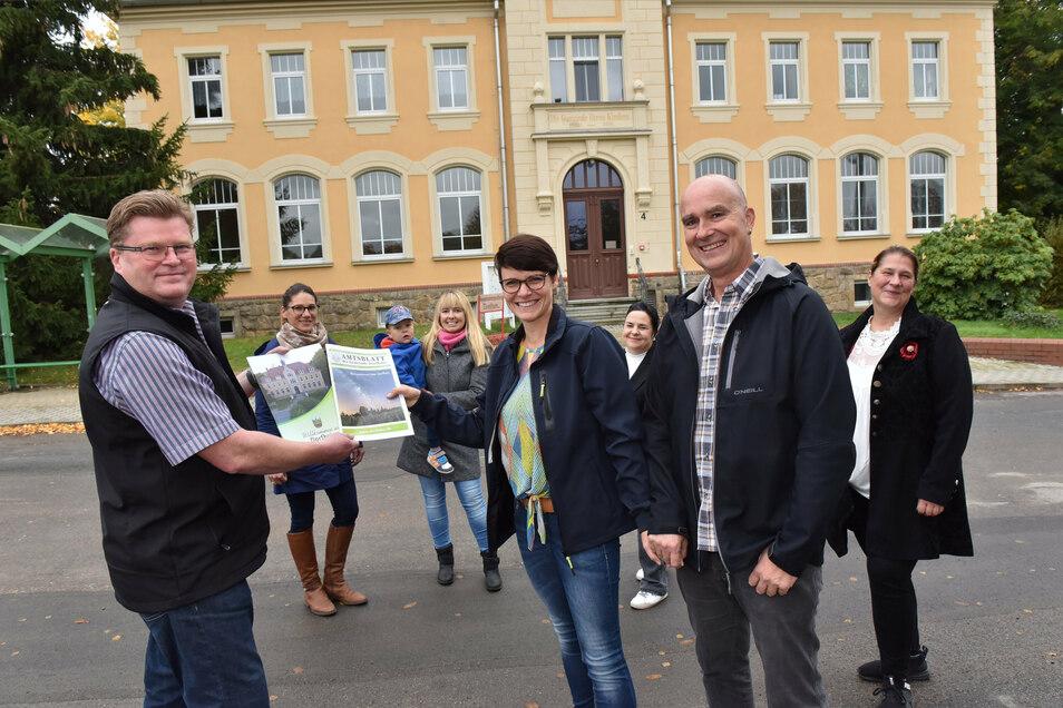 Der Dorfhainer Bürgermeister Olaf Schwalbe (li.) überreicht eine Willkommens-Mappe an Neu-Dorfhainer Sandra Appelt und Greg Ryan.