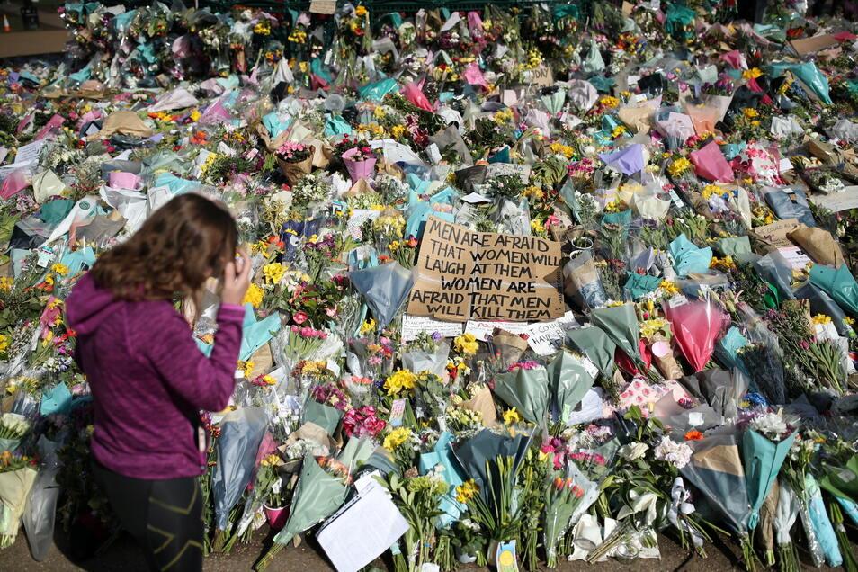 London: Eine Frau schaut sich die Blumen an, die für die getötete Sarah Everard im Clapham Common Park niedergelegt wurden. Die 33-Jährige wurde am 3. März in London entführt und ermordet.