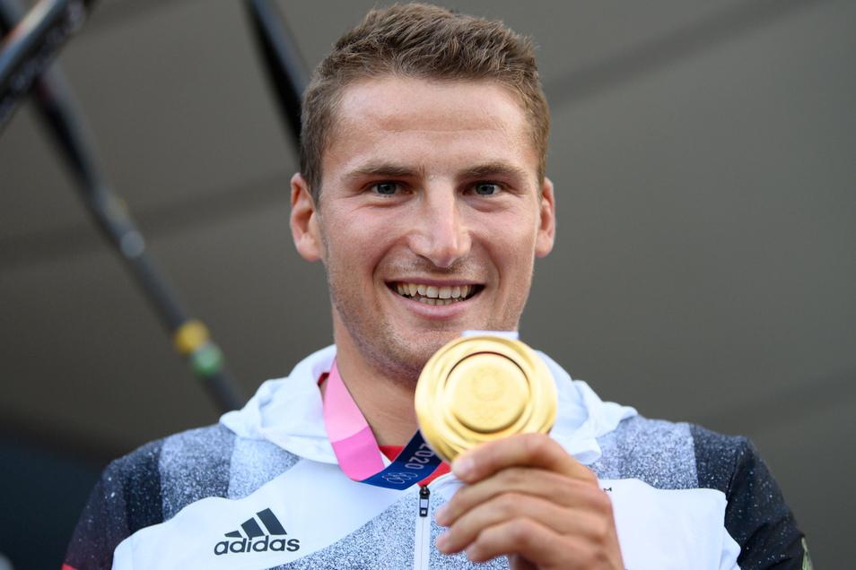 Stolz hält Tom Liebscher die olympische Goldmedaille in die Kamera. Es ist bereits seine zweite.