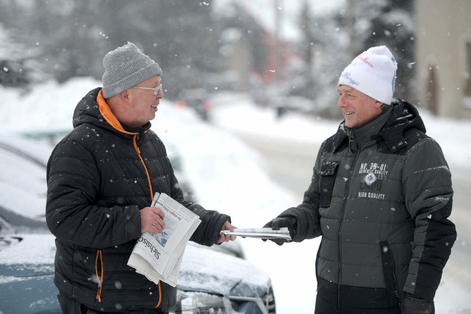 Mathias Schwenke (links) bringt in Oppach und Beiersdorf die Zeitung - auch jetzt im Schneesturm. Matthias Wünsche wartet schon und nimmt sie entgegen.