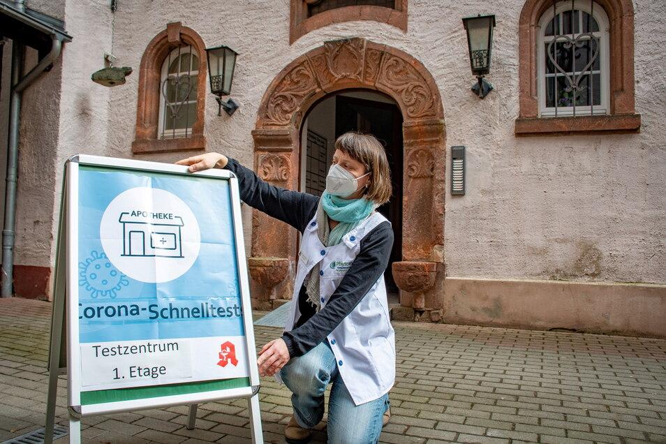 Apothekerin Melanie Pönitz stellt das Schild auf, das Testwilligen in Bergmanns Hof den Weg zu den Räumen weist, in denen die Antigentests vorgenommen werden.